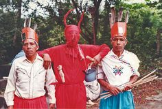 The devil appears with two Huastec men at a fiesta in San Luis Potosi Mexico. The man at right with the bow and arrows is dressed in a woman's costume