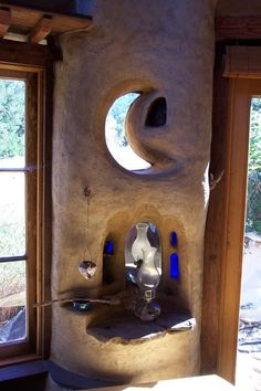 This is what I love about cob... you can shape it into what ever you want. You don't have to frame windows in like this half moon window niche