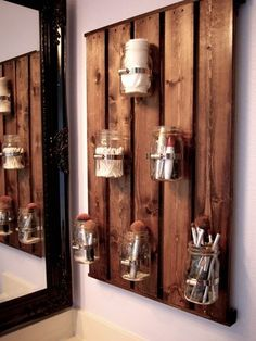 Mason jars attached to a wooden pallet make a farmhouse-chic bathroom storage option that keeps items like Q-tips and cotton balls off the counter.