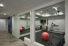 A glass door opens to a basement home gym filled with a mirrored accent wall lined with a corner flat panel tv over a freestanding glass door mini fridge.