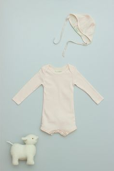 a flora and henri classic onesie in 100% ribbed cotton. lap shoulder design for easy dressing and a button closure...