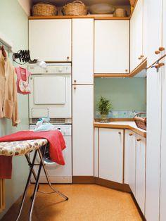 """Zona de lavado y de plancha. Está pensada al milímetro para integrarse dentro del conjunto de los muebles de cocina que, para sacar el máximo partido a la planta rectangular, están distribuidos en forma de """"L"""". Un módulo en columna, tras el fregadero, situado en el ángulo, es ideal para guardar la tabla de la plancha cuando no se usa. Y a su lado, la lavadora y la secadora en columna, una buena opción para rentabilizar mejor el espacio. En la pared, un práctico flexo extensible."""
