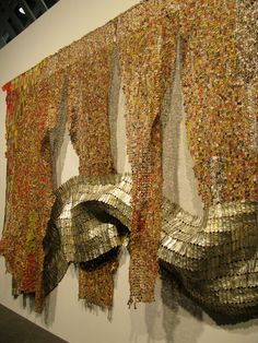 El Anatsui is an artist from Ghana. These tapestries are made with found aluminum and copper wire.
