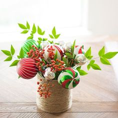 """Ornament Bouquet Christmas Centerpiece - To make an ornament bouquet, remove the silver hanging caps from a variety of ball ornaments and cut florist's foam to fit the bottom of a vase. Then, using 18-gauge florist's wire, stick one end into the ball ornament and the other end down into the florist's foam. Continue until your ornament """"flowers"""" are all attached to the foam. Fill in with cut greenery and berry branches."""
