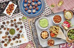 A superfood snack spread: Southwestern Spiced Nuts, Falafel and Italian Veg Balls, Tahini Bliss Balls, Lemon Parsley Cashew Dip, Toasted Coconut Chips, Baked Courgette Fries with Probiotic Ketchup, Chickpea Crunchies, Mung Bean Hummus, radishes and green olives.