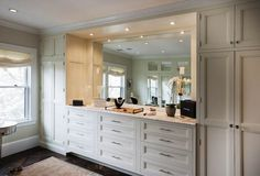 Stunning walk-in closet features floor to ceiling ivory closets framing a built-in dresser with white marble top and built-in mirror over parquet wood floors layered with a light beige rug
