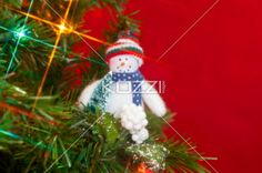 snowman on christmas tree - A white snowman decorated on a christmas tree on a red background