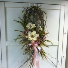 For the ends of the pews - loose vine wreath made with pine, white flowers and pine cones