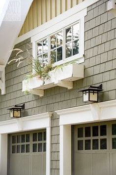 Craftsman garage design ideas - painted wood carriage garage doors, lighting, square windows and charming flower box for added interest.