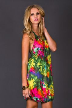 Vibrant 90s style mini dress. An explosion of neon tie dye swirls around this fun summer dress. Sexy details like a plunging back and neck tie halter-top show off a little skin.