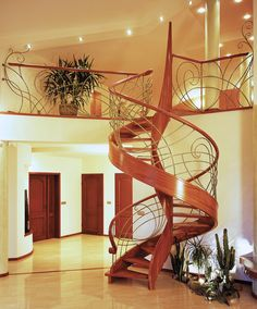 www.trabczynski.com  ST425 Spiralne schody gięte bez podstopni, wykonane z drewna doussie. Ręcznie kute stalowe balustrady, pochwyty drewniane. Realizacja wykonana w domu prywatnym , projekt – TRĄBCZYŃSKI