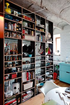 customized kitchen shelf is part wall installation, part storage wonder. Wineglasses, wooden spoons, coffee, spices, design books and much more are stored within its floor-to-ceiling shelves.