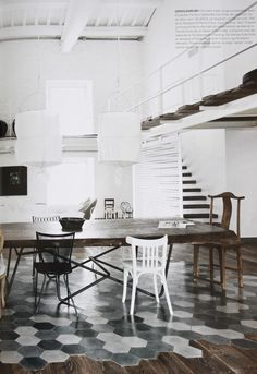 I love this combination of the modern sterile look and the old-fashioned furniture with the floors meshing together in two styles. Beautiful.