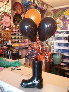 Motorcycle Boot Vase decorated in Harley colors! Great centerpiece and gift!  By: Celebrations Party Store in Abilene, KS. Give us a call at 785-263-3247 to place your order OR find us on facebook at https://www.facebook.com/celebrationspartystore