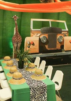 Jungle birthday party decorations can include a fun backdrop, striped table runner, giant animals, and safari hats.Follow us for more planning inspiration or contact us at www.tidesevents.co.uk for help planning your party.