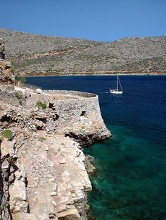 ✯ A pleasure yacht sails past the fortifications on the northern, seaward, side of the Venetian fortress and former leper colony of Spinalonga, in Crete, Greece