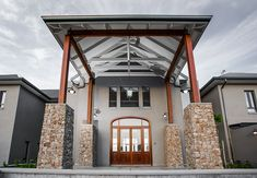 The Main Entrance - a double story entrance with exposed trusses, timber posts and lintels, and custom steel brackets Exposed Trusses, Timber Posts, Thatched Roof, Timber House, Main Entrance, Building A House, Cathedral, Construction, Spaces