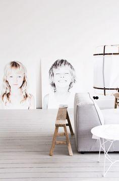 Två stora ljusa porträtt lutade mot en vägg