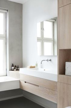 contemporary bathroom, floating white oak cabinets, white sink & tub, dark grey floors, loft apartment in Oslo by Haptic Architects.