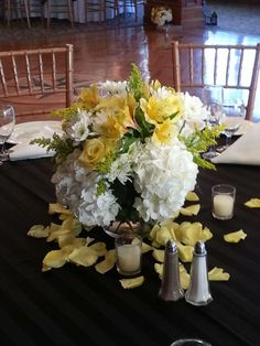 wedding centerpieces of yellow roses, white hydrangea, solidago and white cushions
