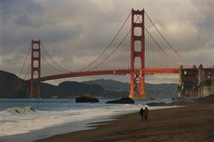 This photograph from the National Geographic collection was taken from the shore near the base of the suspension bridge. A couple strolling on Baker Beach near the Golden Gate Bridge at dawn Wall Art From: National Geographic, by Raymond Gehman from Great BIG Canvas.