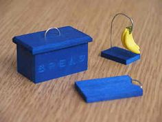 1/12th scale. , , Another accessory for your colour co-ordinated miniature kitchen. , , Here is a set which includes a Bread Bin, with removable lid, a chopping board and a banana hook complete with bananas.