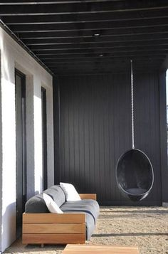 This minimalist home outside of Antwerp was designed by AIDarchitecten with a simple black swing hanging underneath its covered patio.  Photo courtesy of AIDarchitecten