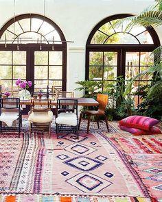 Dans une grande pièce d'inspiration coloniale, avec d'amples baies vitrées, le sol est recouvert de tapis kilim dans des tons roses, et les chaises dépareillées sont habillées de peaux lainées. Décalé.