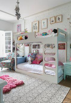 Quarto infantil com beliche, almofadas coloridas e poltrona estampada.