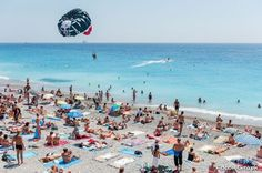 One of the beaches of Nice, where two friends fly with parasailing and temporarily leave the beach full of swimmers and sunscreen.