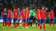 A dejected Kim Young-Gwon of South Korea looks on with teammates