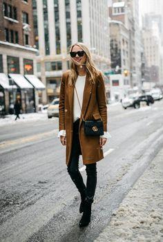 Conjunto abrigo marrón, jersey blanco, pantalones, botas, bolso y gafas negras