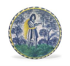AN ENGLISH DELFT PORTRAIT CHARGER  CIRCA 1704-1710, PROBABLY LONDON OR PERHAPS BRISTOL  Painted with a nobleman wearing armor, a yellow sash and cloak, flanked by the initials PM, between sponged trees, within a blue and yellow line and blue-dash rim, on a circular foot  13½ in. (34.3 cm.) diameter