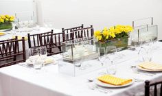 Table linen and centrepieces by Table Art - White weave overlay, yellow printed napkins, rectangle terrarium candle holder on a mirror box table runner. www.tableart.com.au