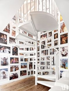 Full-color images immediately take center stage in this otherwise white stairwell in the Miami home of fashion designer Naeem Khan | archdigest.com