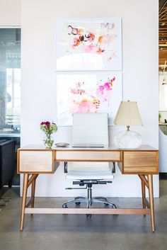 Pink art prints above a midcentury modern wooden desk