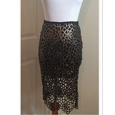 "GORGEOUS SKIRT WITH A BRILLIANT GOLD FOIL SHIMMER This is stunning with a back zip and cutouts with gold shimmer and black lining. Measurements lying flat Waist 12"" Hips 15"" Lining length 13 1/2"" Total length 24"". NWOT Skirts Midi"