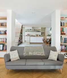Against a herringbone floor, a Knoll sofa is bracketed by two leather-and-wood Falcon chairs by Sigurd Resell in interior designer and av...