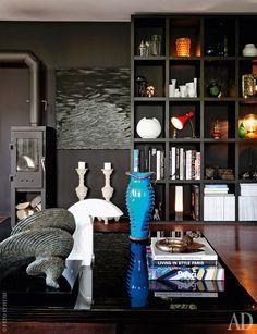 Фрагмент гостиной. На журнальном столике, Minotti, собрано множество декоративных мелочей. На заднем плане книжные полки, сделанные по заказу магазина Pure Living их собственной командой плотников.