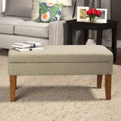 With a comfortable linen top and sleek brown legs, this storage bench is the perfect accent piece to any living room or office. A convenient hinged lid adds space to store your things out-of-sight and in style.