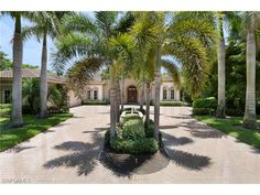 Luxury golf estate home - driveway lined with royal palm trees - beautiful way to welcome family and guests.  Cocoplum Way in Grey Oaks.