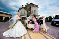 Photo of the bride having the groom stuffed into  the trunk of her car, with help from the bridesmaids!