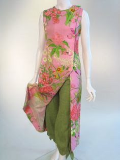 Manchester City Galleries, Item 2009.183  1964 Christian Dior  Boldly floral printed linen tunic dress, fastening full length to the left side with large self fabric covered buttons; green linen harem pants. Labelled 'Christian Dior London Ltd, Modele Originale, made in England' and numbered 14221.