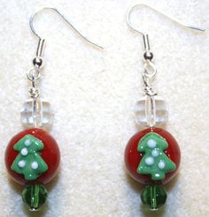 Handcrafted by Teal Palmetto, LLC. Wear a pair of festive Christmas trees on your ears this holiday season!  The glass lampwork Christmas tree beads are joined by clear glass and green glass accent beads to give a simple yet definitively festive look.  These earrings have silver fish hook ear wires. Price: $15.