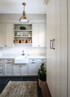 absolutely beautiful minimalist kitchen with dark floors, cream cabinets, neutral decor, potted plant in a basket, lots of natural light