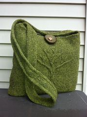 "A beautiful, cabled tree serenely stands guard on the front of this lightly felted bag. It's roughly 13.5""X12"", just the right size for everything you need on the go. You can choose between an I-cord handle (as shown) or a simpler, flat handle. The sample is knit using 4 skeins of Wool of the Andes Worsted Yarn in the gorgeous Rooibos Heather. The closure is the Antler 2"" Toggle. It requires intermediate skills including cabling, knitting in the round and felting."