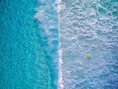Aerial view of a mesmerising blue ocean, via Designspiration.