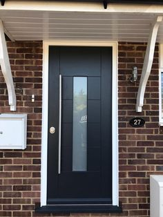 Anthracite grey front door with frosted glass panel and white frames. Long bar handle in brushed chrome for an ultra modern look.