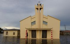 A woman is seen in front of a church in a street flooded by the rising Rio Solimoes, one of the two main branches of the Amazon River, in Anama, Amazonas state, Brazil May 27, 2015. According to the state Civil Defense, more than 237,615 people were affected in the State with strong rains. Picture taken on May 27, 2015. REUTERS/Bruno Kelly
