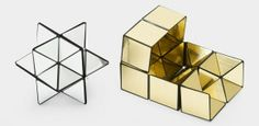 """Cubo de Yoshimoto Nº. 1  El cubo de Yoshimoto fue inventado en el año 1971 por Yoshimoto Naoki, al descubrir que las 8 piezas tripiramidales mencionadas anteriormente del rombododecaedro estrellado, podían ser unidas de tal manera que mostradas de una forma producían el poliedro estrellado, pero al colocarlas de otra se obtenía un cubo. Yoshimoto utilizó este cubo en 1972 en su exposición """"From Cube to Space""""."""